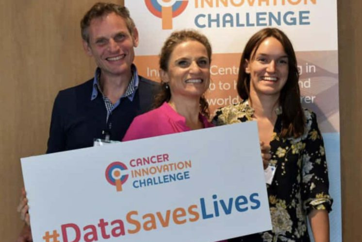 David and Anne holding a Cancer Innovation Challenge banner with #datasaveslives on the banner after winning prize money