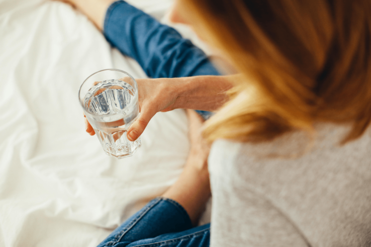 Woman sitting on a bed holding a glass of water