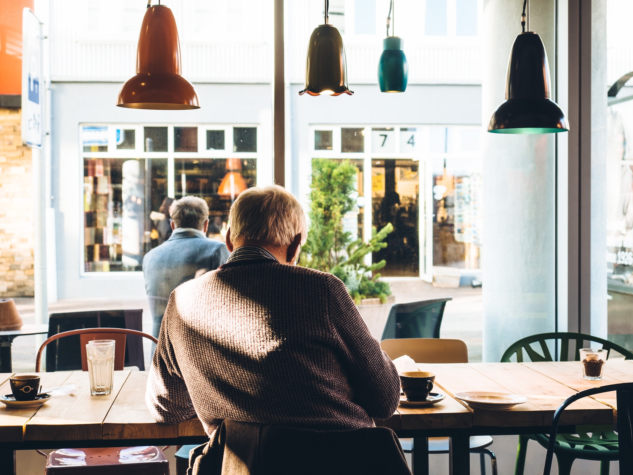 Person sitting at a desk in a coffee shop drinking a coffee